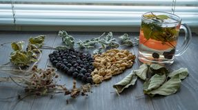 Heart of dried cherries, nuts and dried leaves of tea on the window. Heart of dried cherries, nuts and dried leaves of tea on the wooden window Stock Image