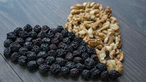 Heart of dried cherries and nuts. On wooden table , side view Stock Photos