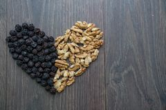 Heart of dried cherries and nuts. On wooden table , top view Stock Photography