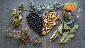 Heart of dried cherries, nuts and dried leaves of tea on the window. Cup of herbal tea Royalty Free Stock Image