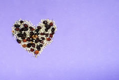 Heart from dried flowers. Pink, violet purple background Stock Photography