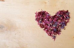 Heart of dried flowers on a wooden background stock image