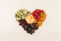 Heart of dried fruits closeup on beige wooden background. Decorative composition for Valentine`s Day. Top view Royalty Free Stock Photos