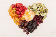 Heart of dried fruits closeup on beige wooden background. Decorative composition for Valentine`s Day. Top view Stock Images