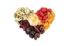 Heart of dried fruits closeup on white wooden background. Isolated. Decorative composition for Valentine`s Day. Top view Stock Photos