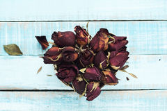Heart from dried roses on blue parquet planks Stock Photo