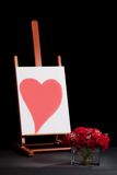 Heart on easel and roses. Studio still life of a red heart painted on canvas on a wooden easel with a dozen red roses against a black background stock photography