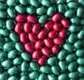 Heart from Easter eggs. Red heart on green background made from colourful chocolate Easter eggs royalty free stock photo