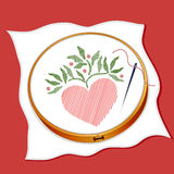 Heart Embroidery. Embroidered folk art style heart design on white cloth in a wooden embroidery hoop, needle & thread, red background Royalty Free Stock Images