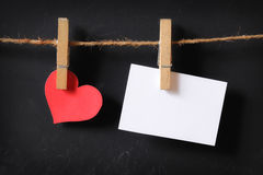 Heart with empty poster hanging. With blackboard background Royalty Free Stock Photo