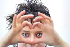 Heart on eyes. Women with heart sign made of fingers Stock Photography