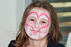 Heart face painting. Headshot portrait of of cute little girl with heart shaped face painting royalty free stock image