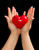 Heart in female hands. Over black background Stock Image