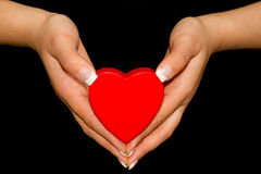 Heart in female hands. Over black Royalty Free Stock Photo