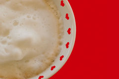 Heart filled cafe latte for romantics. Red hearts border the rim of a white cup topped with foam with red background for copy Royalty Free Stock Images