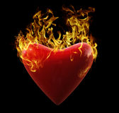 Heart on Fire. A 3D Red glossy heart on fire isolated on black background Stock Photos