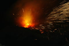 Heart on fire. Sparks flying when starting to lance the tap-hole of a submerged arc furnace, with heaps of casting sand to the front, at a South African producer Royalty Free Stock Image