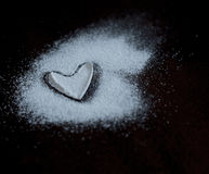 Heart flour. Heart of flour on the black background royalty free stock image