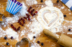 Heart of flour, rolling pin, berries and utensils for baking on wooden background.Happy Valentine`s Day. Love and home