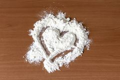 Heart of flour on wooden table, cooking with love concept stock image