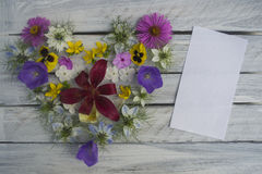 Heart of flowers with a note on wooden surface 7 stock images