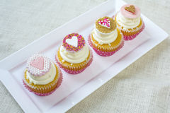 Heart fondant with sprinkles on vanilla cupcake for valentines. Valentine's french vanilla cupcakes with heart gumpaste topper in white square ceramic plate stock photography