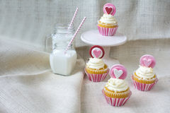 Heart fondant vanilla cupcake and glass of milk. Vanilla cupcake with heart gum paste topper. Valentine's party treat with glasses of milk on natural burlap stock image