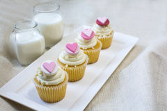 Heart fondant vanilla cupcake and glass of milk. Vanilla cupcake with heart gum paste topper. Valentine's party treat with glasses of milk on natural burlap royalty free stock images