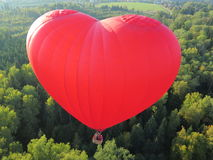 Hot air ballon of the forest. Flying in a hot air balloon in the shape of heart Royalty Free Stock Image