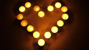 Heart form burning tea lights. Tea light candles forming the shape of a heart. Love theme concept. Romantic background. Heart form burning tea lights. Tea light stock footage