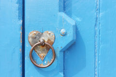 Heart formed backplate of door handle. Detail of old blue door with heart formed backplate of door handle Royalty Free Stock Image