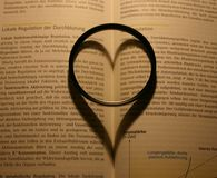 Heart formed shadow. Heart-fomed shadow of a lens on a book stock illustration