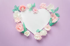 Heart frame with color paper flower. Festive flower composition with color paper flowers with greeting card on the purple background. Flat lay, overhead view Stock Photo
