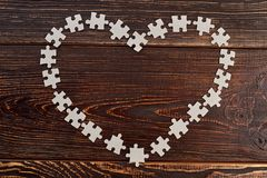 Heart frame made from cardboard puzzles. Shape of heart from blank jigsaw puzzles on dark wooden background. Love to game Stock Photography