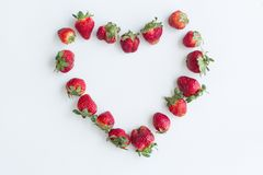 Heart frame made of strawberries on white background. Flat lay, top view, copy space, centered royalty free stock photos