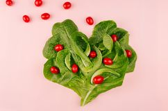 Heart of fresh leaves greens salad and cherry tomatoes on pink background. Cheerful modern spring food Royalty Free Stock Photos