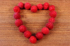 Heart of fresh raspberries on wooden table, symbol of love Stock Images