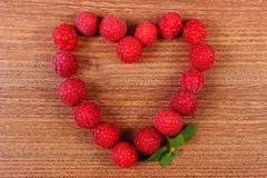 Heart of fresh raspberries on wooden table, symbol of love Stock Photography