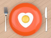 Heart fried egg in orange  plate Royalty Free Stock Photography