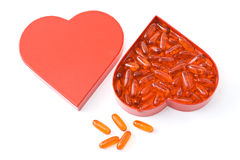 Heart friendly fish oil capsule. Fish oil pills in heart shaped box on white backgroud Royalty Free Stock Photo