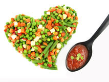 Heart of a frozen mixed vegetables. With tomato souse in spoon stock image