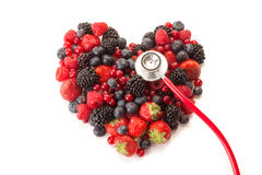 Heart of fruit with a stethoscope. Mixed fruit in the shape of a heart with a stethoscope, placed on a white background Stock Photography