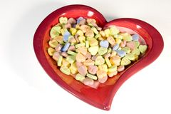 Heart full of candy. A red valentines heart dish full of candy hearts Stock Image