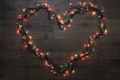 Heart of garland. Glowing garland lights dark background wire Stock Photography
