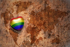 Heart with gay flag on a vintage world map crack paper background. Stock Photos