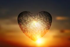Heart geometric shape on sunset sky Stock Images