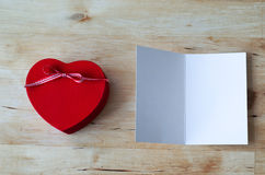 Heart gift Box and Blank Card. Overhead shot of a painted red wooden heart shaped gift box with ribbon bow, and an opened greeting card, left blank for a message Royalty Free Stock Images