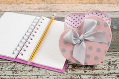 Heart gift box and notebook on vintage wood table Royalty Free Stock Photos
