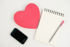 Heart gift box phone and notebook on white background Stock Image