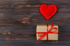 Heart and gift box with red ribbon on wooden background royalty free stock images